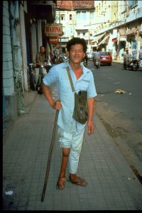 man with crippled leg from a polio infection standing on a sidewalk