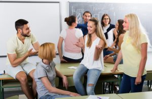 Group of students sit and stand in the front of a classroom and talk.
