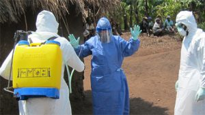 Two epidemiologists get decontaminated in the field.