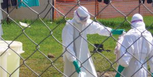 Two healthcare workers in hazard suits spray an infected area
