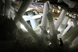 Large gypsum crystals in a mine with a man standing among the crystals.