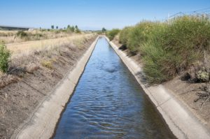 An irrigation channel with water running through a farm.