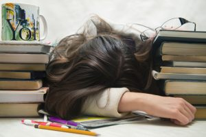 girl with her head on a desk with books