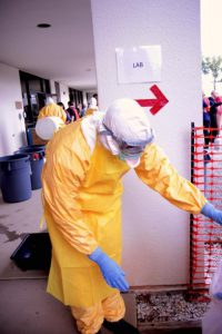 Healthcare worker dressed in protective clothing observes safety protocols in dealing with viruses.