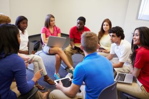 Students with laptops sit in a group.