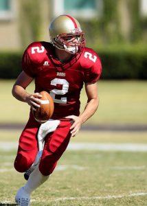 A football player runs on a field with a football