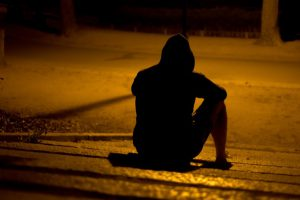 person sits by a street in the dark