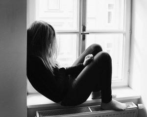 girl sitting slumped against a wall