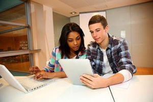 A female and a male student sit at a desk and work on classwork