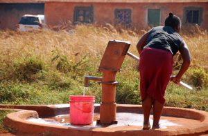 Woman pumps water from a village well.